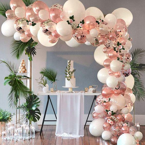 Arco descontruído de balões com folhas naturais